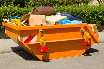 Container mit Sperrmüll auf Straße mit Absicherung